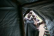Seventeen-year-old Nyabuol Tut lifts up the plastic sheet of her tent as she holds her two-year-old daughter, Nyalit, inside Bidibidi refugee settlement in northern Uganda. Nyabuol was gang-raped by Dinka soldiers twice, both in December 2015 and March 2017. She gave birth to Nyalit from the first rape by four soldiers and is eight months pregnant from the second rape by seven armed Dinka men. Her parents were shot to death by Dinka soldiers in between both conflicts in 2013 and 2016.