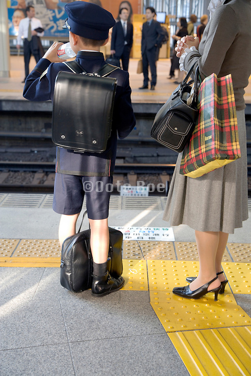 elementary school child standing with his mother waiting for the train to arrive Tokyo Japan