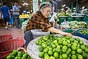 19 OCTOBER 2012 - BANGKOK, THAILAND:   A woman sorts and grades limes in the Bangkok Flower Market. The back of the market is also used to sell fruit and produce. The Bangkok Flower Market (Pak Klong Talad) is the biggest wholesale and retail fresh flower market in Bangkok.  The market is busiest between 3:30AM and 6AM. Thais grow and use a lot of flowers. Some, like marigolds and lotus, are used for religious purposes. Others are purely ornamental.         PHOTO BY JACK KURTZ
