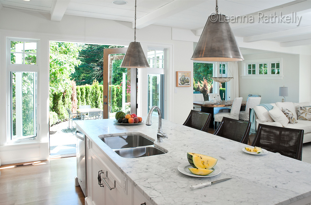 This Island home kitchen features a large white marble island, pendant lights and a large double sink.