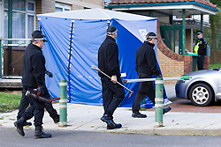 © Licensed to London News Pictures. 06/10/2012. Walsall , UK . Police walk in front of a blue tent at the scene . Police and forensic examiners investigate after two bodies were found at a block of flats . A woman was found inside a flat in Holly Court , Acacia Avenue , Walsall and a man was found dead outside the block . Photo credit : Joel Goodman/LNP