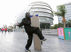 A participant in fancy dress holding a cardboard skyscraper poses in front of City Hall, London, during The Great Gorilla Run.