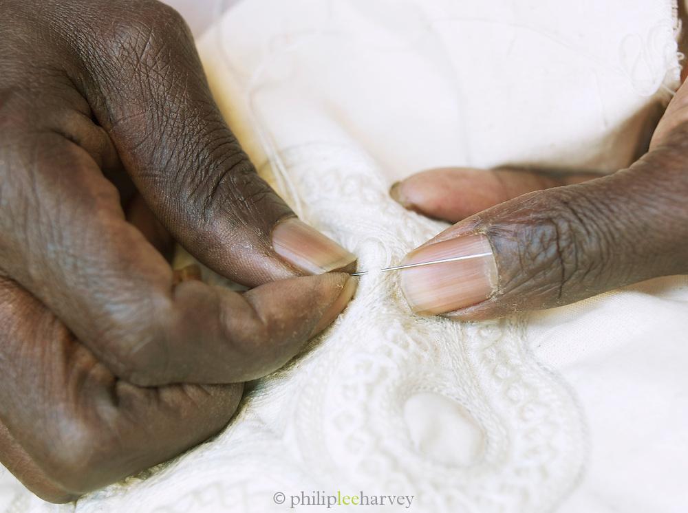 A needlework man sews a detailed pattern in Djenné, Mali