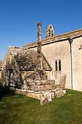 Building exterior of historic church of Saint John, Inglesham, Wiltshire, England, UK 13th century with 15th century churchyard cross