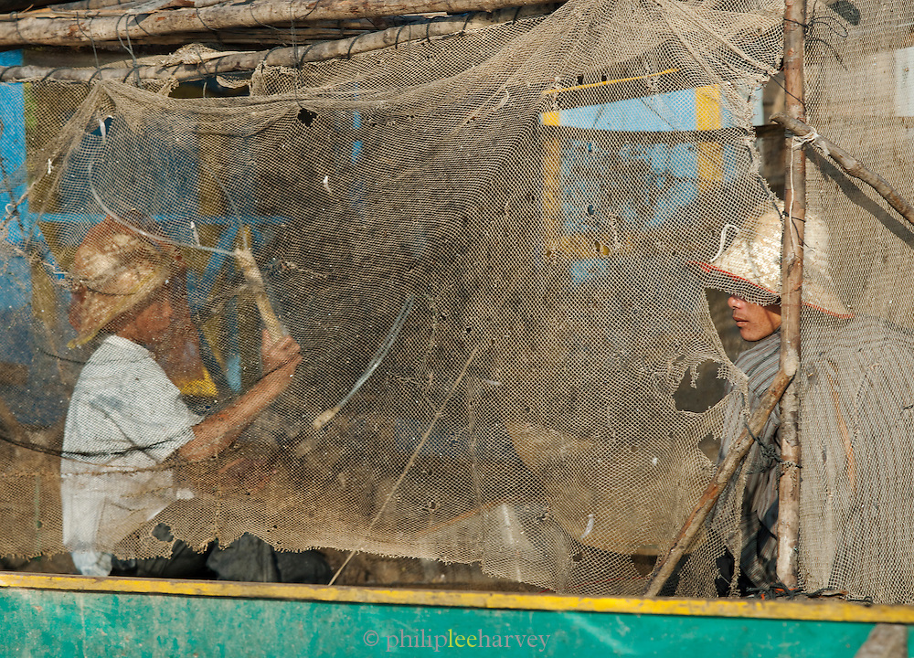 Fishermen behind old nets in a floating village community on the great Tonlé Sap lake, Cambodia