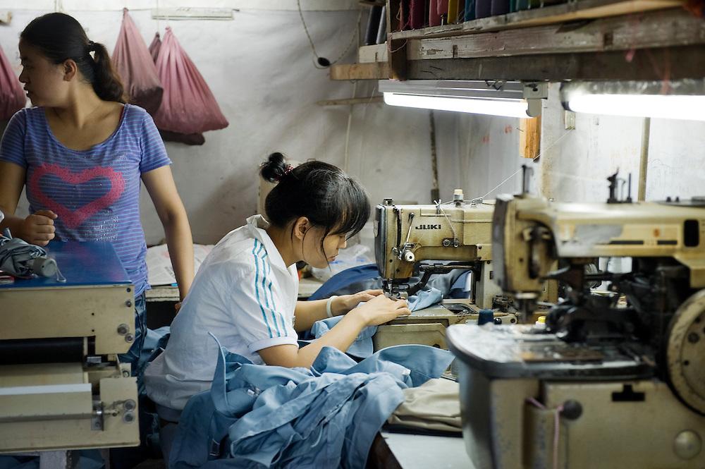 China, Shanghai,  26 aug 2010.Kledingatelier..Jonge vrouwen naaien op electrische machines kleding in een atelier..Foto (c)  Michiel Wijnbergh