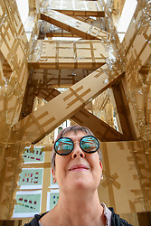 © Licensed to London News Pictures. 21/07/2019. LONDON, UK.  A visitor views the inside of The People's Tower, a monumental cardboard structure, built by artist Olivier Grossetête aided by a local volunteers, stands in Guildhall Yard.  Over 1,000 boxes have been used to build the 20m high artwork, inspired by the Guildhall building.  The four day construction process culminates in the structure being ceremonially torn down.  Photo credit: Stephen Chung/LNP