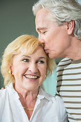 Mature man kissing mature woman on forehead, smiling
