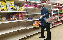 © Licensed to London News Pictures. 27/10/2021. London, UK. A shopper picks a last pack Walkers crisp from nearly empty shelves in Sainsbury's, north London, as food shortages continue, following Brexit. According to the British Retail Consortium, three in five retailers expect prices to increase in the run up to Christmas, and the ongoing labour shortages are making the situation worse. Photo credit: Dinendra Haria/LNP