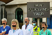Extinction Rebellion nurses and doctors standing in front of New Scotland Yard appear to have taped their mouth with ducktape to highlight their freedom of expression is violated. They staged a protest outside Metropolitan Police HQ, London on Wednesday, Sept 9, 2020 - to highlight their resistance after healthcare professionals were threatened with disciplinary action for speaking out about their work during the coronavirus outbreak. Environmental nonviolent activists group Extinction Rebellion enters its 9th day of continuous ten days protests to disrupt political institutions throughout peaceful actions swarming central London into a standoff, demanding that central government obeys and delivers Climate Emergency bill. (VXP Photo/ Vudi Xhymshiti)