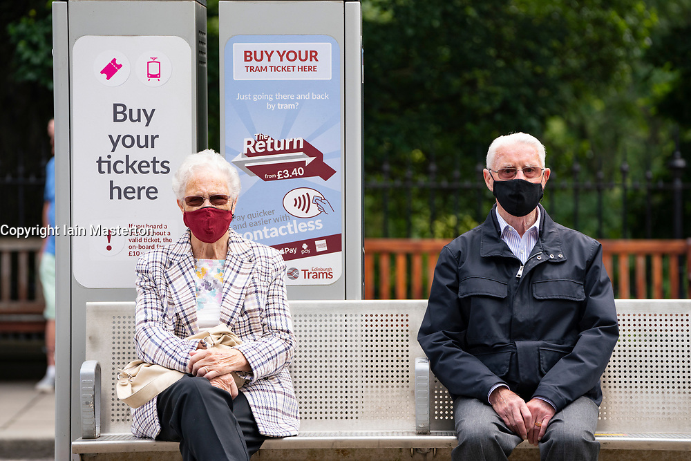 Edinburgh, Scotland, UK. 24 July, 2020. Senior couple sitting at tram stop social distancing themselves and wearing facemasks.  Iain Masterton/Alamy Live News