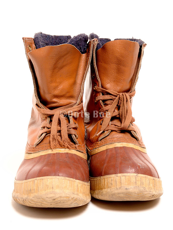 A pair used cold weather boots against a seamless background