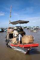 """Cai Rang Floating Market is one of the largest in the Mekong Delta. The vendors at these markets are boats of all different sizes. Cai Rang is open all day but it is busiest from sunrise to about 9 am. The main items sold there are fresh produce from Cai Rang and neighboring areas. Every boat has a long upright pole at its bow on which samples of the goods for sale are hung as a form of """"advertisement"""". Larger boats anchor and create lanes that smaller boats weave in and out of. The waterway becomes a maze of boats packed with mangos, bananas, papayas and pineapples."""