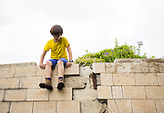 Young boy of ten sites on a wall.<br /> Humpty Dumpty sat on a wall,<br /> Humpty Dumpty had a great fall<br /> All the king's horses and all the king's men<br /> Couldn't put Humpty together again.