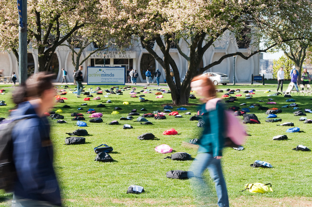 Marquette students pass by a display of 1,100 backpacks that represent the number of college students lost annually to suicide. The display helps raise awareness of college student suicides.