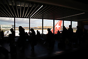 Silhouette view of passengers waiting in the terminal building for their Swiss Air flights from London City Airport in London, England, United Kingdom. London City Airport is an international airport located in the Royal Docks in the London Borough of Newham, east of the City of London in the Docklands area. It is an incredibly convenient airport for business travel.