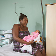 INDIVIDUAL(S) PHOTOGRAPHED: Fenelie Ponolle (left) and unknown (right). LOCATION: St. Damien Hospital, Nos Petits Frères et Sœurs, Tabarre 41 Commune, Haïti. CAPTION: Fenelie Ponolle, a 33-year-old mother, sits with her little girl, born three days earlier at St. Damien Hospital.