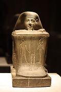 Block statue of Hor, priest of the god Amun in the temple of Karnak. Greywacke. 23 Dynasty 755 BC
