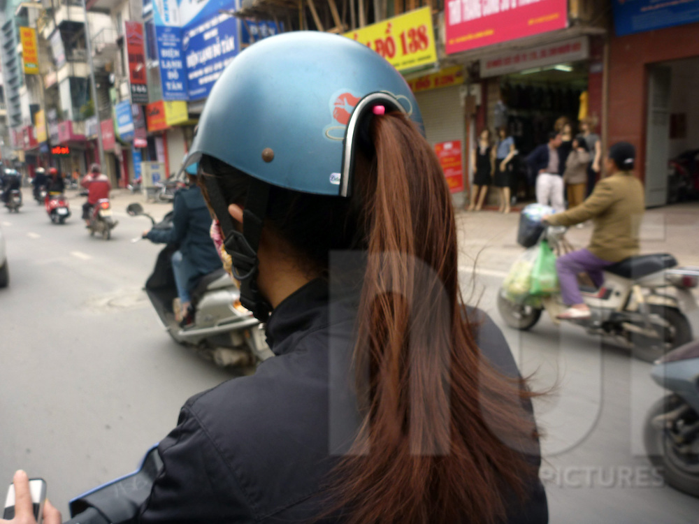 New kind of helmets are made to allow women to wear ponytails while riding on a motorbike. Hanoi, Vietnam
