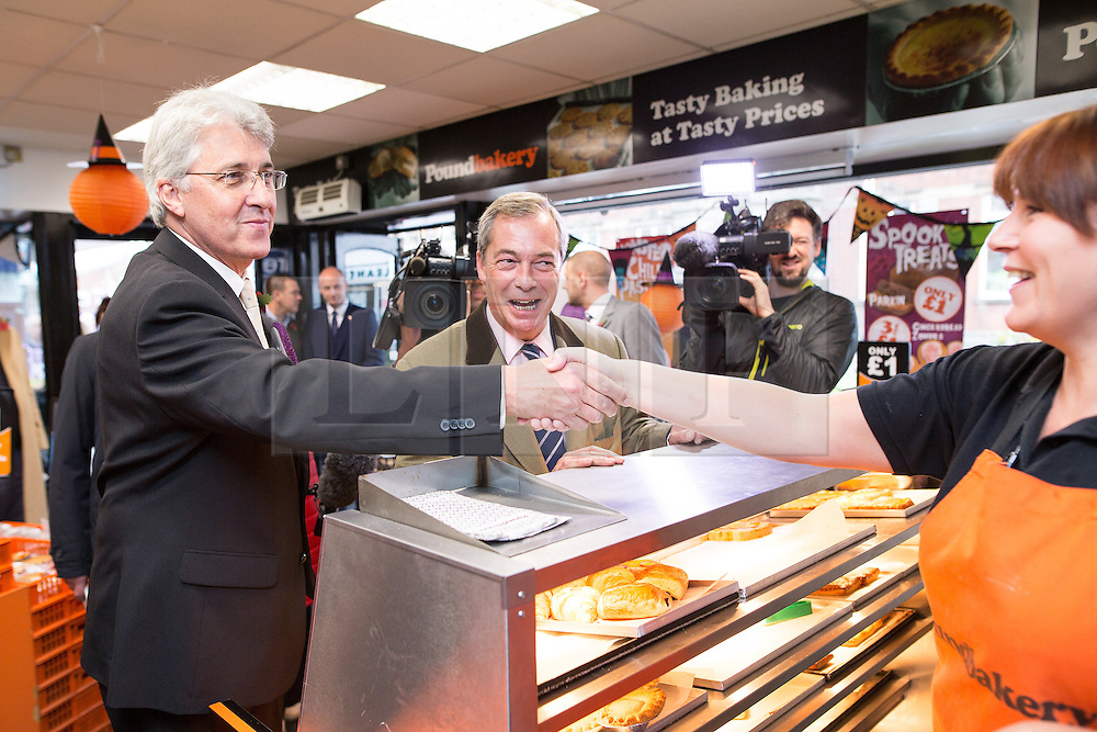 © Licensed to London News Pictures . 03/11/2015 . Oldham , UK . UKIP leader NIGEL FARAGE (c) with candidate JOHN BICKLEY (l) buying two pies for a pound at the Pound Bakery in Royton Shopping Centre , at the launch of the party's campaign for the seat of Oldham West and Royton . The by-election has been triggered by the death of MP Michael Meacher . Photo credit : Joel Goodman/LNP
