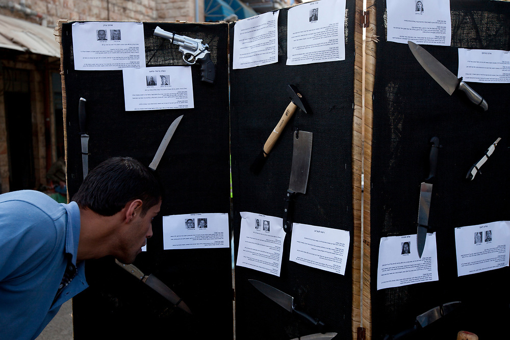 A man looks at texts containing detailed information about   women murdered by their male spouses and partners across Israel over the past year, which are displayed next to a model of the weapon used in each case, during a memorial rally for the murdered women, at the Mahane Yehuda Market in Jerusalem, on November 25, 2010.