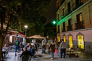 People sitting outside eating dinner and having drinks at a bar on the Plaza del Dos de Mayo next to the green cross sign of a pharmacy on the 31st of October 2019 in Madrid, Spain.