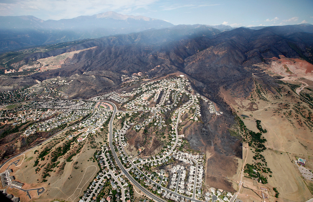 The burned area of hundreds of totally destroyed homes in the Waldo Canyon fire is seen from the air with Pikes Peak in the background in Colorado Springs, Colorado June 28, 2012.  Cooler temperatures and lighter winds helped firefighters on Thursday in the battle against the fire, which has destroyed hundreds of homes and forced more than 35,000 people to flee. REUTERS/Rick Wilking (UNITED STATES)