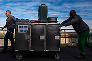 Prisoners transport food in special containers and bread crates from the main kitchen through the prison to a wing to be served.  HMP/YOI Portland, Dorset, United Kingdom.