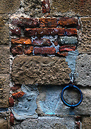 A close up view of a wall in Monitcchiello, Tuscany, with a horse tie ring on it
