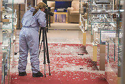 © licensed to London News Pictures. London, UK 06/06/2013. A forensic officer photographing the damage left after an armed robbery at Selfridges on Oxford Street, London. Photo credit: Tolga Akmen/LNP