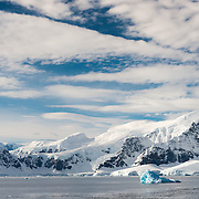Blue sky and clouds abaove the dramatic mountainous landscape of the Gerlache Strait on the Antarctic Peninsula.
