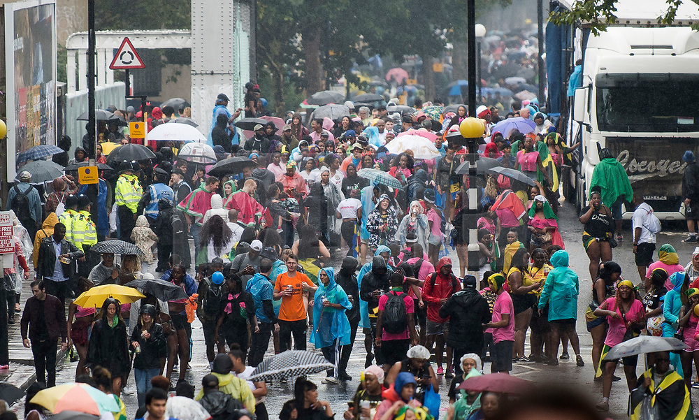 © Licensed to London News Pictures. 26/08/2018. London, UK. Thousands of carnival goers under umbrellas and rain coats, brave the wet and windy conditions at family day of the 2018 Notting Hill Carnival. Up to 1 million people are expected to attend this weekend's event that is one of the worlds largest street festivals. Photo credit: Ben Cawthra/LNP