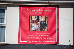 © Licensed to London News Pictures. 27/02/2021. Marston Moretaine, UK. A sign on the side of the Post Office as The funeral cortege carrying the coffin of Captain Sir Tom Moore passes through his home town of Marston Moretaine, on it's way to Bedford Crematorium for a funeral service. Captain Tom, who raised £32 million pounds for the NHS by walking laps of his garden during Coronavirus lockdown, died in hospital aged 99. Photo credit: Ben Cawthra/LNP