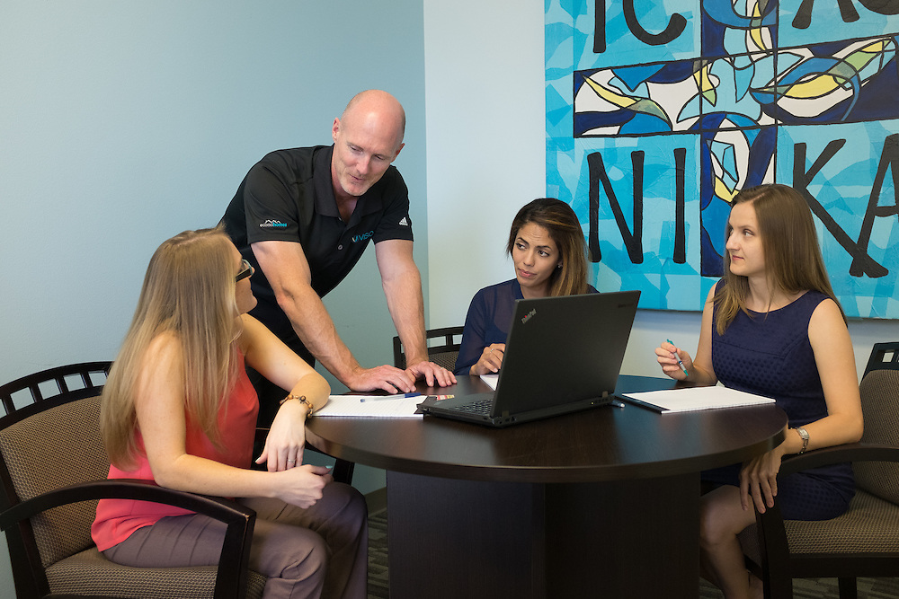 Jeff Ball (standing), President and CEO of Visio Financial Services in Austin, Texas, meets with ( l-r) Lydia Adams, Marketing Manager, Martha Barreda, Account Executive and Yulia Yahin, Human Resources.