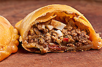Beef Empanada fill close up.  The Empanada is a pastry turnover filled with a variety of savory ingredients and baked or fried.