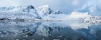 Stortind mountain peak reflects in icy water of Flakstadpollen, Kilan, Flakstadøy, Lofoten Islands, Norway