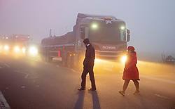 © Licensed to London News Pictures. 27/11/2020. <br /> Blackheath, UK. Two people crossing the A2 Shooters Hill Road on Blackheath Common, London. Freezing foggy weather conditions this Friday morning across large parts of the UK. Photo credit:Grant Falvey/LNP