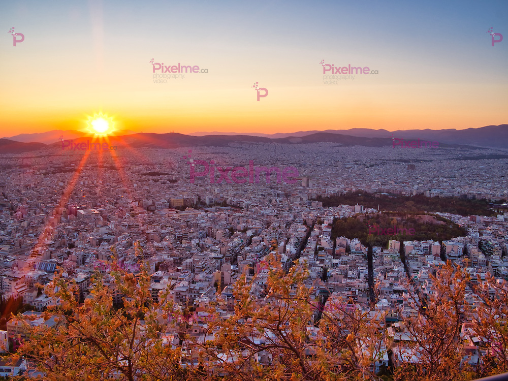 Aerial view of sunset sky above white city of Athens with clear sky and red sunbeams