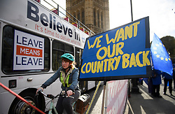 "© Licensed to London News Pictures. 14/01/2019. London, UK. A bus displaying the words ""LEAVE MEANS LEAVE"" passes Pro EU, anti Brexit campaigners as they gather outside the Houses of Parliament in London the day before MPs vote of British Prime Minister Theresa May's deal on leaving the EU. Photo credit: Ben Cawthra/LNP"