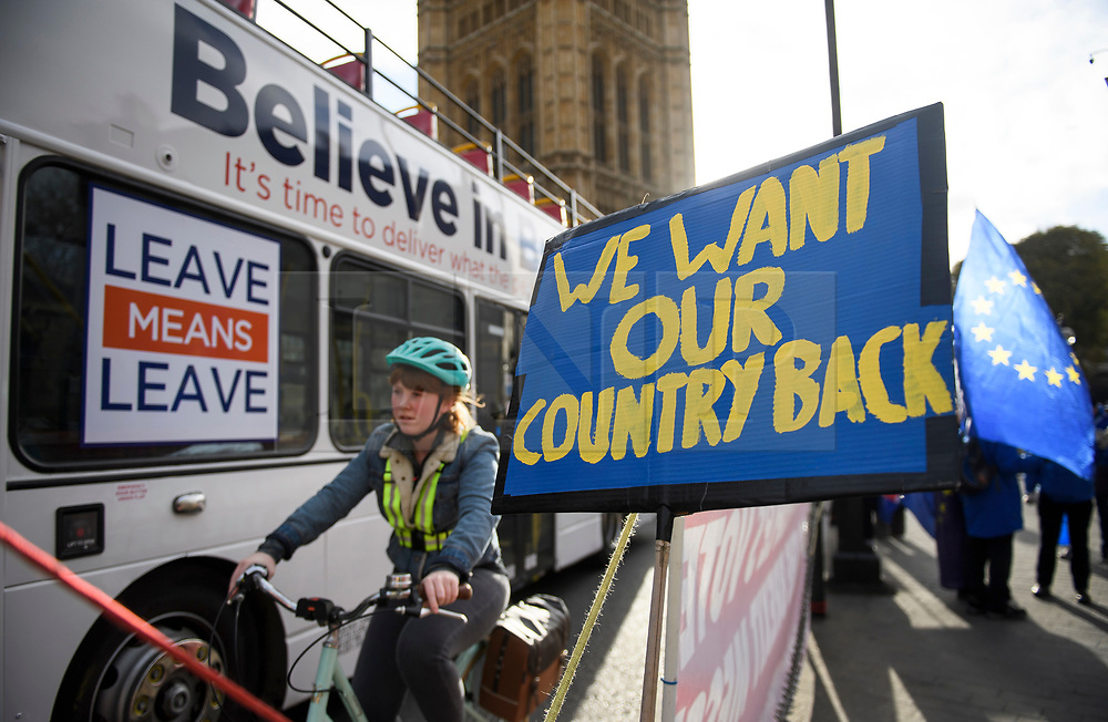 """© Licensed to London News Pictures. 14/01/2019. London, UK. A bus displaying the words """"LEAVE MEANS LEAVE"""" passes Pro EU, anti Brexit campaigners as they gather outside the Houses of Parliament in London the day before MPs vote of British Prime Minister Theresa May's deal on leaving the EU. Photo credit: Ben Cawthra/LNP"""