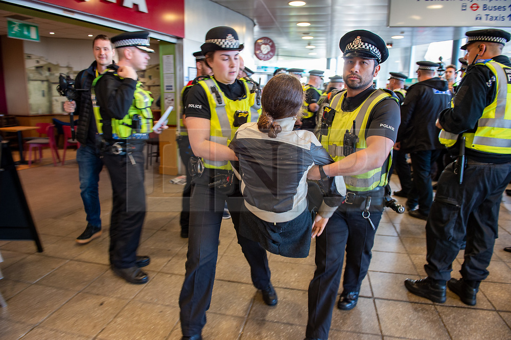 © Licensed to London News Pictures. 10/10/2019. London, UK. Extinction Rebellion protesters are removed by police. Protesters arrived via the Docklands Light Rail and proceeded to conduct a sit-in to block the entrance from the train station to the London City Airport. Photo credit: Peter Manning/LNP