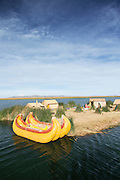 Traditional Totora reed boat tied up on a Small family island, one of the Floating islands of Lake Titicaka, Puno, Peru, South America