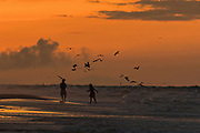 A couple chases birds along the beach at dawn on a cloudy morning June 5, 2017 in Folly Beach, South Carolina. Folly Beach is a quirky beach community outside Charleston known to locals as the Edge of America.