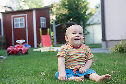 Little cute baby boy sitting on grass and laughing in a lawn, Munich, Bavaria, Germany