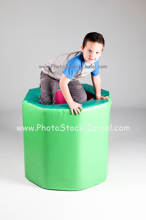 Indoor playground young boy climbs out of a foamrubber barrel  On white Background