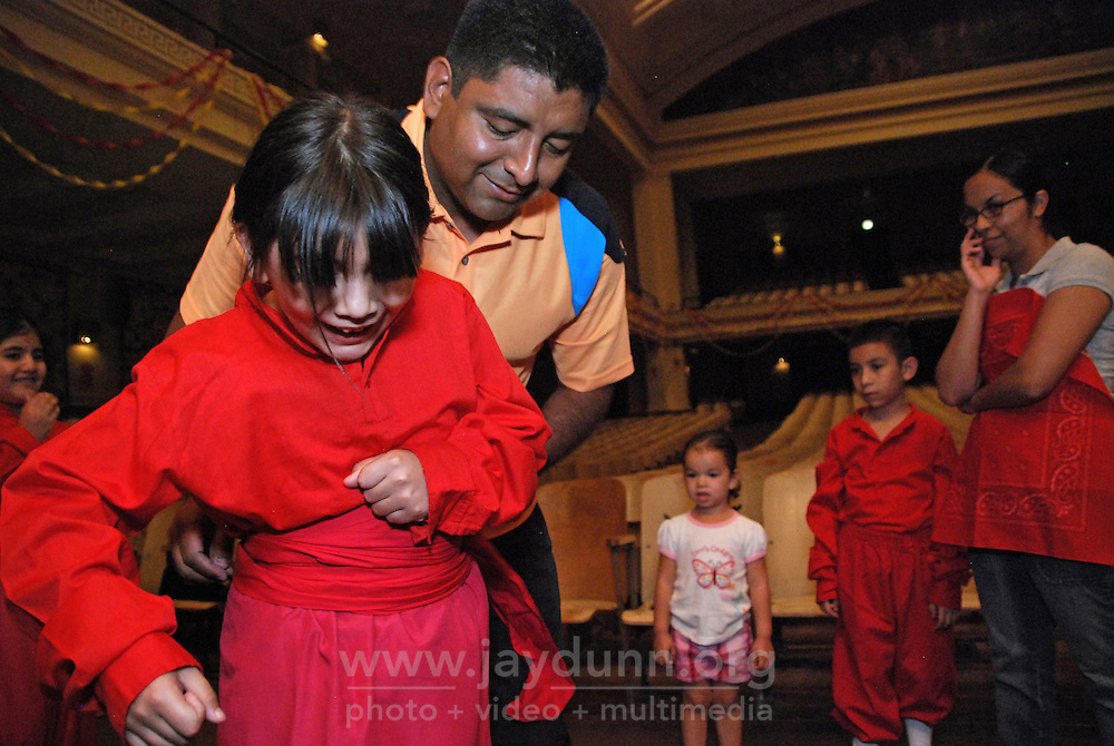 """USA, Chicago, July 2nd - 23rd, 2009.  Professional instructor Ruben Pachas, who is Peruvian, helps a dancer put on her costume before a dress rehearsal. For almost 20 years, Polo Garcia, a professional dance teacher from """"America Baila,"""" has been giving traditional South American dance lessons at various Pilsen and Little Village schools, including Maria Saucedo Scholastic Academy, whose turn-of-the-century auditorium is featured here. Garcia, who is Mexican, does the research for these dances in-person, makes the costumes himself, and provides free summer classes. He works with Claudio Rabadan, a former Saucedo student.  Photographs for HOY by Jay Dunn."""