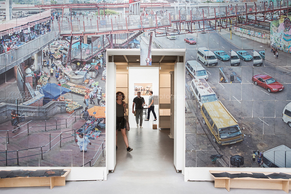 """VENICE, ITALY - 4 JUNE 2016: Visitors walk through the Evidence Room, between the """"design workshop : sa"""" exhibit room (seen here) and Souto Moura Arquitectos exhibit room at the 15th Venice Architecture Biennale in Venice, Italy, on June 4th 2016.<br /> <br /> The Evidence Room exhibition, presented by the University of Waterloo lead by Canadian scholar Robert Jan Van Pelt and, is a reconstruction of key architectural elements of Auschwitz that disproved the Holocaust denier David Irving who had sued American scholar Deborah Lipstadt and her publisher for libel.  In her 1994 book Denying the Holocaust: The Growing Assault on Truth and Memory, Lipstadt counted Irving among Hitler apologists and revisionists seeking to downplay the scale of the Holocaust and the systematic murder of six million European Jews. <br /> <br /> Robert Jan van Pelt served as the expert witness in the trial, and his report became one of the sources of inspiration for the new discipline of architectural forensics, which is located at the intersection of architecture, technology, history, law and human rights.<br /> <br /> The exhibition, which force us to examine architecture used for evil – and designed by architects complicit in crimes against humanity, reconstructs some of those forensic details, including full-scale models of a gas column, a gas door, and a wall section with gas-tight hatch – all of which were shown in court to prove beyond a reasonable doubt that Auschwitz was, as Van Pelt says, """"a purposefully designed factory of death, equipped with large, homicidal gas chambers and massive incinerators."""""""