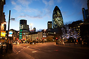 Night time scene in the City of London. 1 St Mary Axe, also knowns as The Gherkin in the City of London. This iconic building is one of the best loved buildings in London with it's distinctive bullet like shape and twisted glass exterior. As night falls, the building glows against the sky as it also fades yet is still a bright blue.