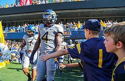 Sep 11, 2021; Morgantown, West Virginia, USA; West Virginia Mountaineers running back Leddie Brown (4) gives high fives to young fans as he walks onto the field prior to their game against the Long Island Sharks at Mountaineer Field at Milan Puskar Stadium. Mandatory Credit: Ben Queen-USA TODAY Sports