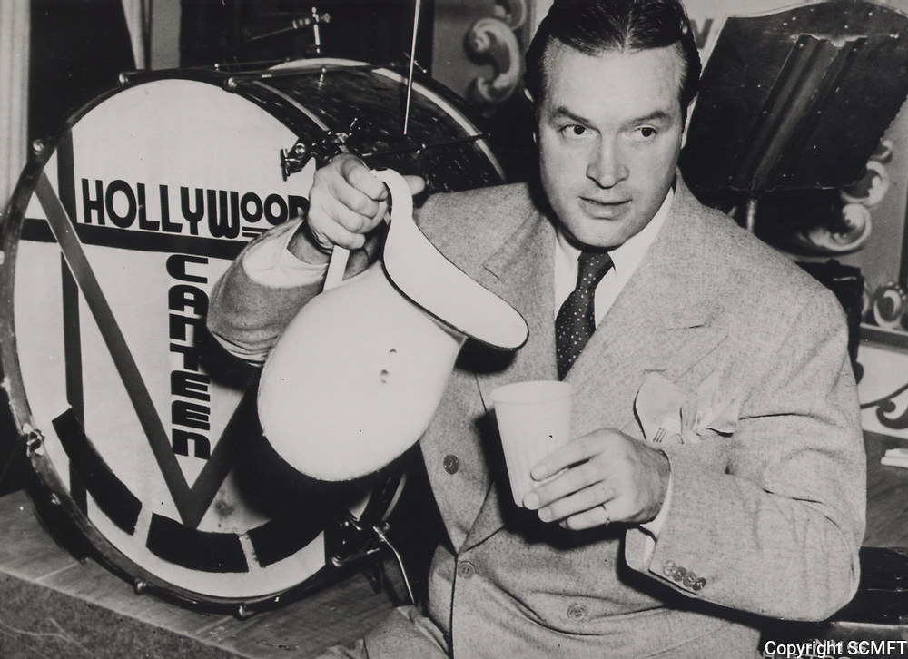 1944 Bob Hope pours some water while sitting on stage at the Hollywood Canteen.